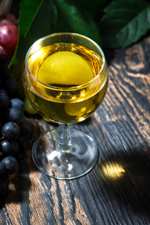 glass of white wine on wooden background, vertical, closeup Stock Photo