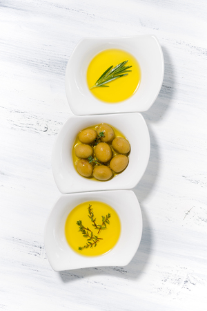 cooking oil: assortment of different types of olive oil in white bowls, vertical Stock Photo