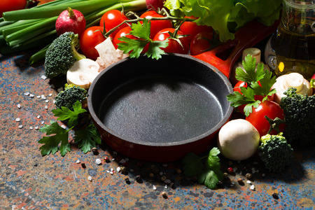 cooking oil: empty cast iron skillet and fresh organic vegetables, closeup, horizontal