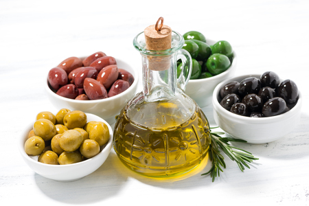 cooking oil: bottle with olive oil and bowls with olives on white wooden table, top view, horizontal Stock Photo