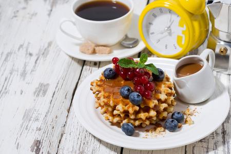 Wafels met bessen en karamel voor het ontbijt op een witte achtergrond, horizontaal