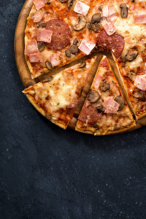 junk: Pizza with cheese and sausage on a black background, vertical