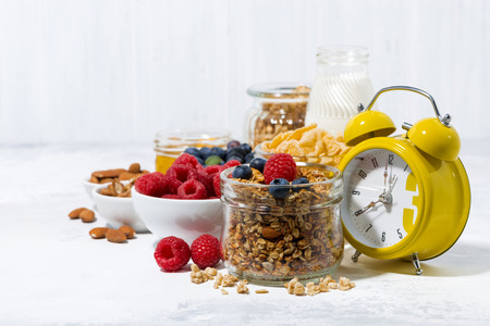 healthy products for breakfast, granola and berries on white background, horizontal