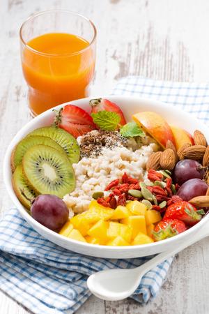 oatmeal porridge, with fresh fruit, orange juice and superfoods, vertical, closeup