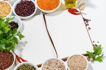 book for recipes, spices and assortment of legumes, closeup