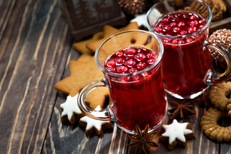Christmas hot cranberry tea and cookies on dark background, top view, horizontal