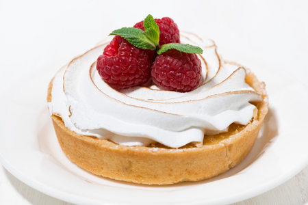 sweet tartlet with meringue and raspberry on white plate, closeup