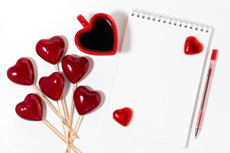 Decorative hearts on sticks, cup of coffee and notepad on a white background, top view closeup