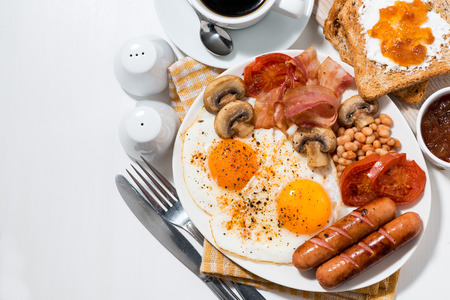 English breakfast of scrambled eggs with bacon, sausages and vegetables, top view, horizontal Stock Photo