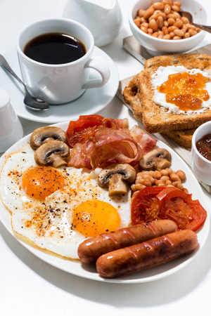 English breakfast of scrambled eggs with bacon, sausages and vegetables, vertical closeup Stock Photo