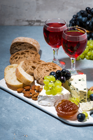 cheese plate, fresh ciabatta, grapes and two glasses of red wine, vertical photo 写真素材 - 114064362