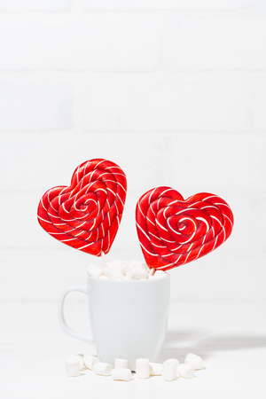 candy on a stick in the form of hearts in a cup on white background, vertical top view Stock Photo