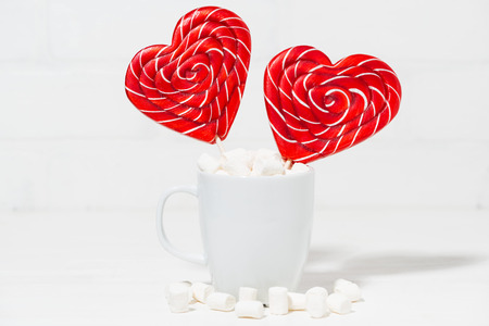 candy on a stick in the form of hearts in a white cup, closeup horizontal