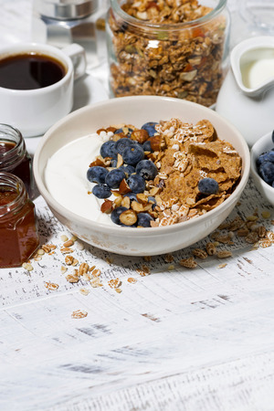 Bowl of healthy wholegrain flakes, yogurt and fresh blueberries on white table, vertical top view Фото со стока