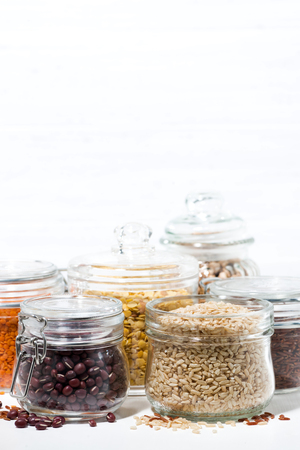 assortment of various cereals and legumes on white background, vertical closeup