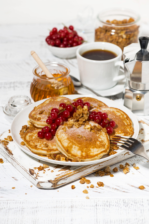 Delicious pancakes with berries and honey for breakfast on white table, vertical closeup