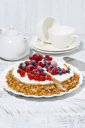 Healthy sweet oatmeal cake with yoghurt and fresh berries on white table, vertical photo