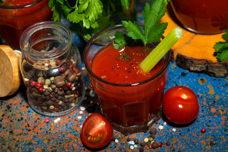 Fresh tomato juice with salt and celery, top view horizontal