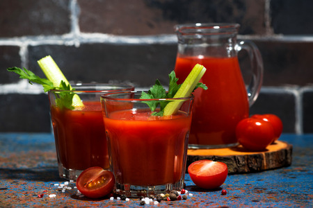 Fresh tomato juice with salt and celery on dark table, closeup horizontal