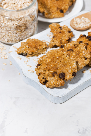 Homemade oatmeal cookies with raisins on white wooden board, vertical top view Stock Photo