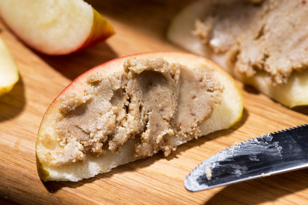 Homemade peanut butter on a piece of apple, closeup