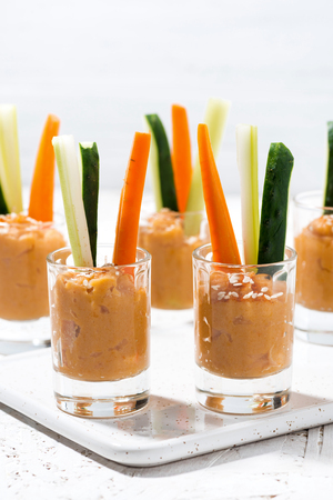 Healthy snack - pumpkin hummus and fresh vegetables, vertical closeup Stock Photo