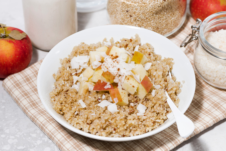 Healthy breakfast quinoa with apple and coconut, closeup