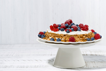 Healthy sweet oatmeal cake with yoghurt and fresh berries on a stand, horizontal