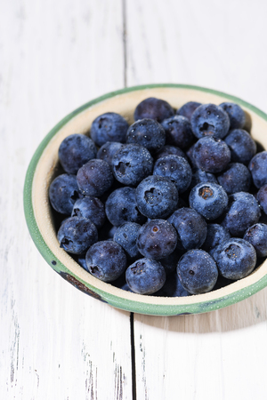 Fresh juicy blueberries in a bowl, vertical closeup