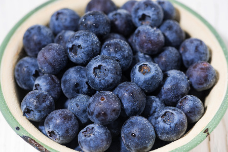 Fresh juicy blueberries in a bowl, closeup top view Stock Photo