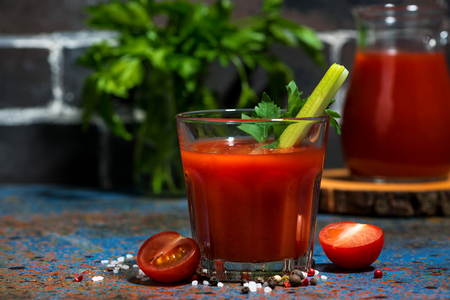 Healthy tomato juice with salt and celery on dark table, closeup horizontal