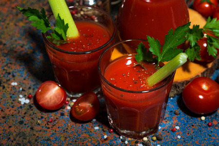 Fresh tomato juice with celery in glass cups, top view horizontal