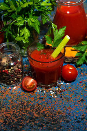 Fresh tomato juice with salt and celery on dark table, top view