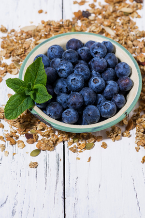 Fresh juicy blueberries and homemade granola, vertical closeup