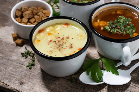 Hot soups in mugs on wooden table, top view Stock Photo