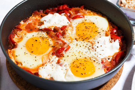 Shakshuka fried eggs in a pan, closeup Stock Photo