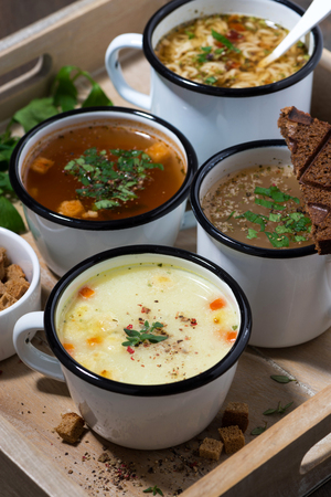 Hot soups in mugs on wooden tray, vertical top view
