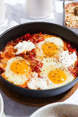 Shakshuka fried eggs in a pan, vertical top view