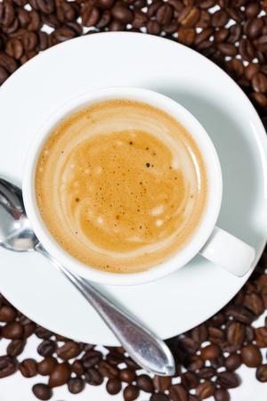 Espresso cup on coffee beans, closeup vertical Reklamní fotografie