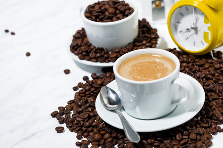 Espresso cup on coffee beans on white