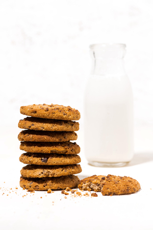 Oatmeal cookies with chocolate chips on a white  and a bottle of milk, vertical closeup