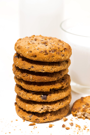 Oatmeal cookies with chocolate chips on a white  and a glass of milk, vertical closeup Reklamní fotografie