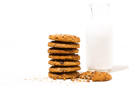 Oatmeal cookies with chocolate chips on a white   and a bottle of milk, horizontal Reklamní fotografie