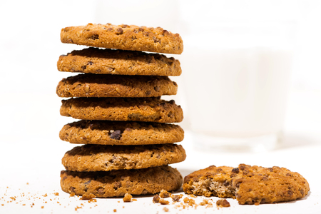 Oatmeal cookies with chocolate chips on a white  and a glass of milk, closeup horizontal Reklamní fotografie