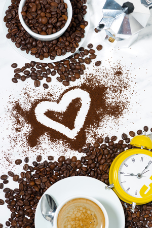 Espresso cup, alarm clock, heart and coffee beans conceptual photography, vertical Reklamní fotografie