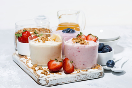 Słodkie jogurty z owocami i jagodami na pyszne śniadanie na białym stole, poziomo