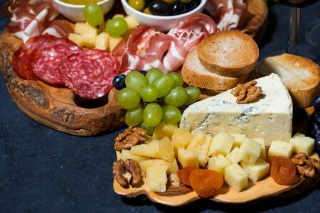 Cheese platter on a wooden board, bread, fruit and cold cuts, closeup