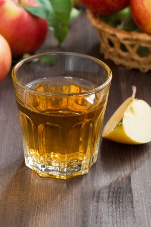 Autumn drink - apple cider or juice in a glass, vertical, close-up