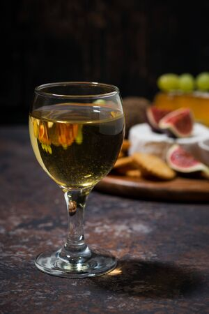 glass of white wine and snacks on dark background, vertical closeup