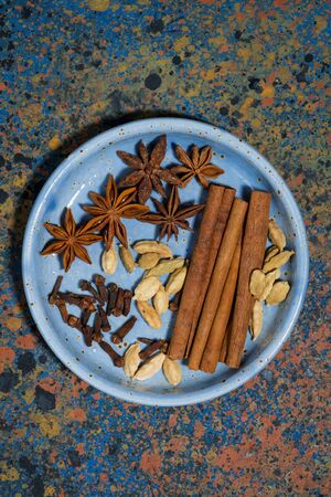 spices for masala tea in a plate, top view
